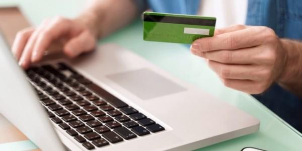 jovem-empresario-segurando-um-cartao-de-credito-e-usando-laptop-para-e-commerce_403156-59